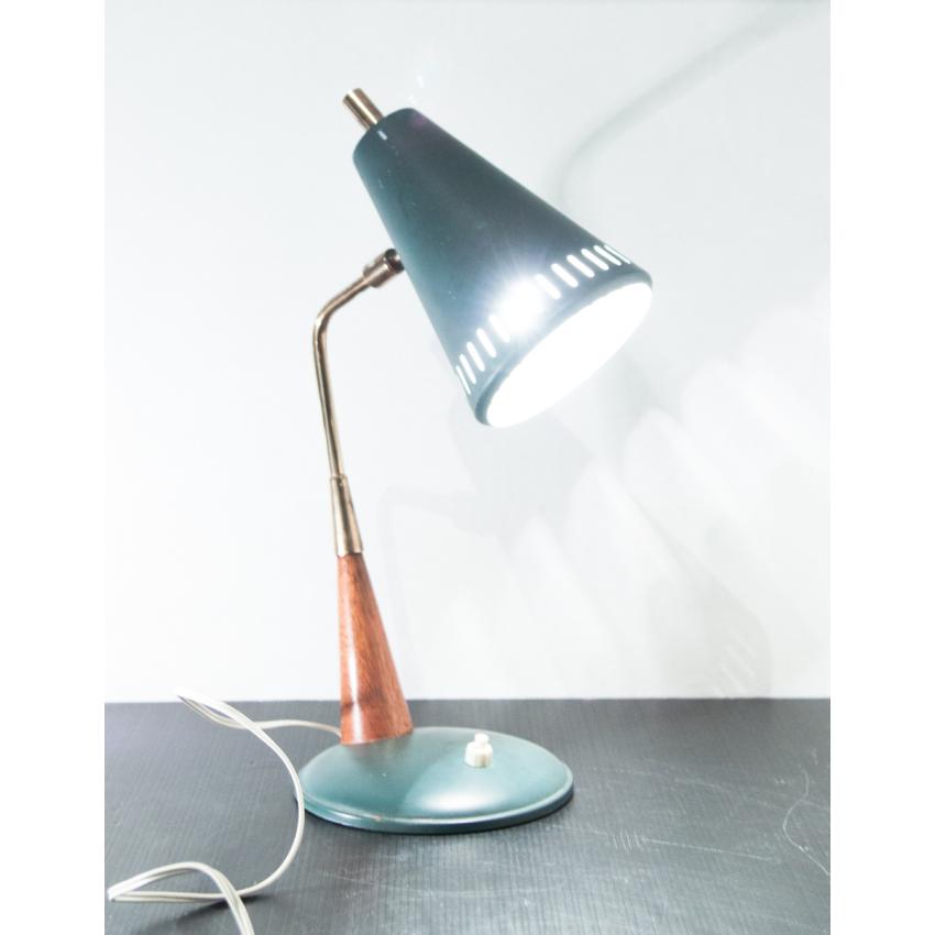 Petite lampe de bureau en fer, laiton et bois comportant un réflecteur conique aux perforations oblongues.